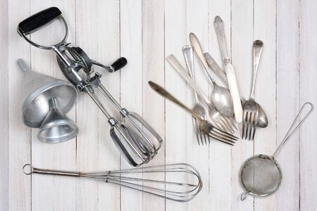 beater: Overhead shot of a group of old kitchen utensils on a rustic wood kitchen table.