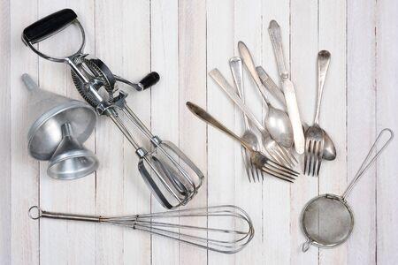 batidora: Tiro de arriba de un grupo de utensilios de cocina antiguos en una mesa de cocina de madera rústica.