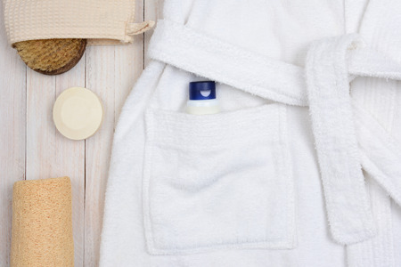 Closeup of a bathrobe with lotion in the pocket. A scrub brush and soap and a luffa are next to the robe on a rustic wooden surface.