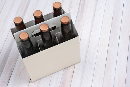 6 pack beer: High angle shot of a blank six pack of brown beer bottles on a rustic white wood table. Horizontal format with copy space. Stock Photo