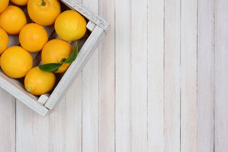 A crate of fresh picked lemons on a rustic white wood table in the upper left corner of the frame. Horizontal format with copy space. Stock Photo