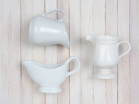 high angle: Closeup of three white ceramic pitchers on a rustic whitewashed wood table. High angle shot in horizontal format.