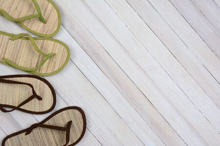 high angle shot: High angle shot of two pairs of flip flops on a wood background. Set to the left side of the frame leaving room for your copy. Stock Photo