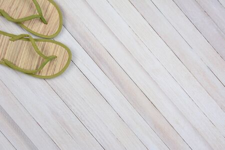 high angle shot: High angle shot of a single pair of summer flip flops on white wood surface. The sandals are in the upper left corner leaving room for your copy.
