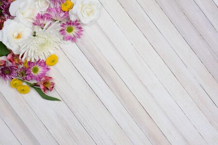 high angle shot: High angle shot of a bunch of flowers in the upper left corner of the frame. Colorful spring time flowers on a rustic white wood table with copy space. Stock Photo