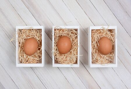high angle shot: Three brown eggs in wood crates on a whitewashed wood surface. High angle shot in horizontal format.