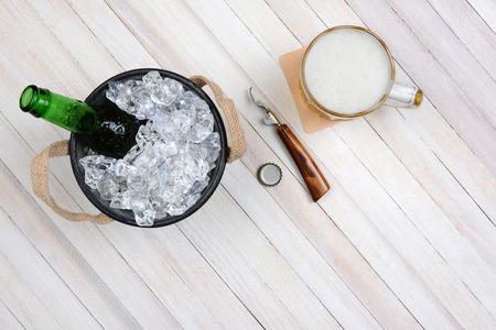 overhead shot: Overhead shot of an ice bucket with an opened beer bottle, a mug of beer and opener on a rustic white wood table. Horizontal format with copy space. Stock Photo