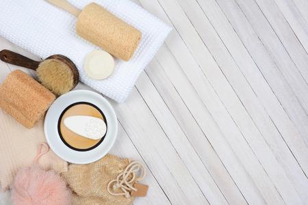 Bad och Spa stilleben. Hög vinkel skott av badrumstillbehör, inklusive, handduk, tvål, luffa och sandaler på en rustik vitt trä yta. Poster är inställda på den vänstra sidan lämnar utrymme för ditt exemplar. Stockfoto
