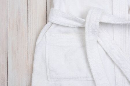 bath: High angle closeup shot of a white terry cloth bathrobe on a rustic white wood surface. Horizontal format with copy space.