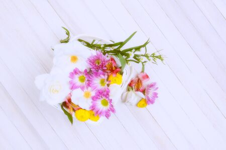 Basket of Spring flowers on a wood table. Overhead shot with intentional high key effects applied. Horizontal format with copy space. Stock fotó