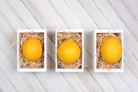 high angle shot: High angle shot of three wooden boxes each with a single lemon on a bed of straw. The wooden crates are on a rustic wood table.
