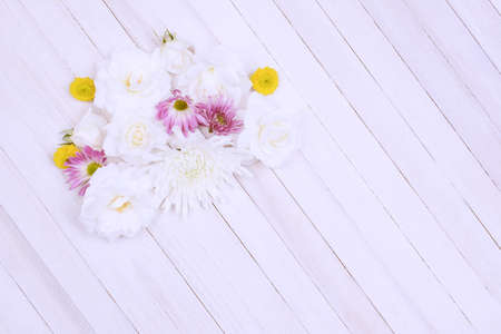 A group of pastel Spring flowers on a wood table. Overhead shot with intentional soft focus and high key effects applied. Horizontal format with copy space.