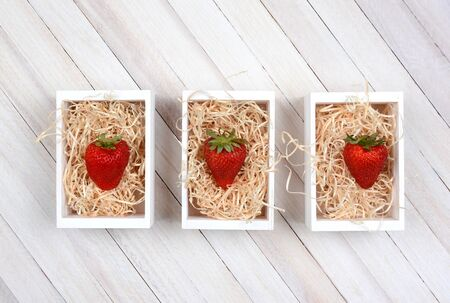 high angle shot: Three mini wood crates filled with straw each with a single large ripe strawberry. High angle shot on a rustic whitewashed wood table with copy space.