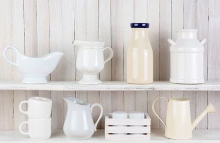 Closeup of two white wood rustic kitchen shelves with assorted household items.  Stock Photo