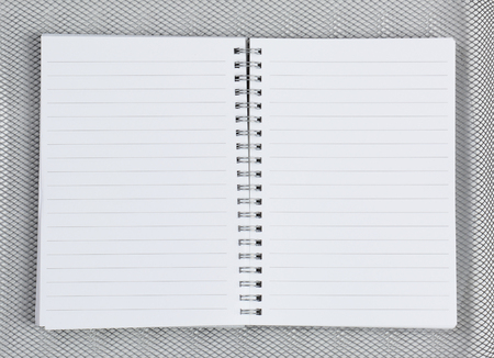 high angle: High angle shot of an open notebook on a silver mesh background. Stock Photo
