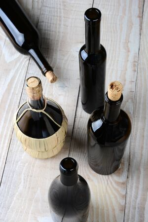 high angle shot: High angle shot of assorted wine bottles on a white rustic wood table.