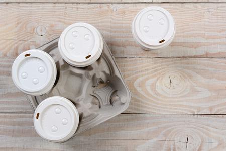 白い木製の無作法なテーブルにコーヒー キャリアを段ボール取るの高角度のショット。コピー スペース付き水平フォーマットです。