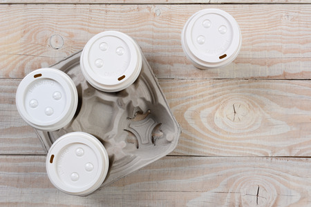 four objects: High angle shot of a cardboard take out coffee carrier on a white wood rustic table.Horizontal format with copy space.