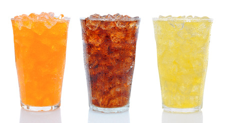 Closeup of three glasses of soda, Cola, Orange and Lemon Lime on white with reflection. Filled with ice the glasses are covered with condensation