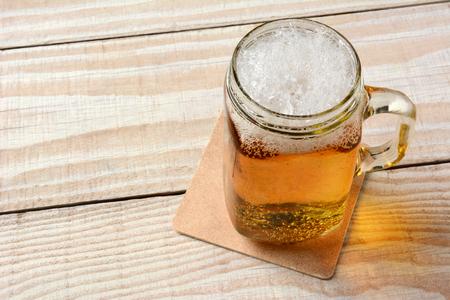 jarra de cerveza: Alto ángulo de cerca de un frasco de vidrio lleno de cerveza en una mesa de madera rústica. Foto de archivo