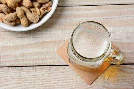 jarra de cerveza: Cacahuetes y cerveza Naturaleza muerta en una mesa de madera blanca rústica. Foto de archivo