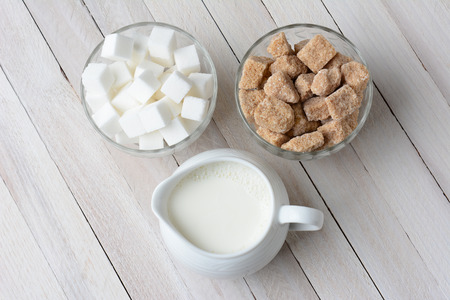 High angle shot of two bowls of sugar cubes, white and natural, and a pitcher filled with cream. Horizontal format on a rustic wood table.