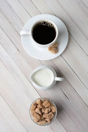creamer: High angle shot of a cup of coffee, cream pitcher, and a bowl of natural sugar cubes. Vertical format on a rustic whitewashed table.