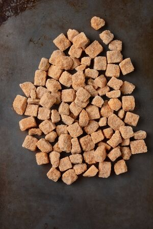 unprocessed: High angle view of a pile of brown natural sugar cubes on a used metal baking sheet. Vertical format.