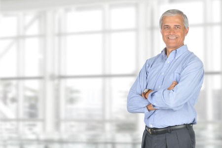 casually: A smiling casually dressed mature businessman standing in front of a large modern office window.