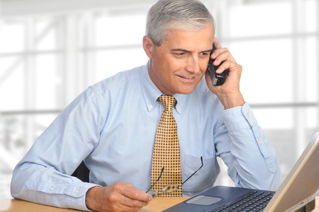 A mature salesman talking on the telephone