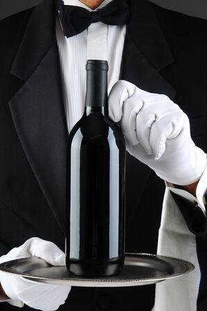 camarero: Primer plano de un camarero que llevaba un esmoquin y guantes blancos, sosteniendo una botella de vino en una bandeja de servir. Formato vertical. El hombre es irreconocible.