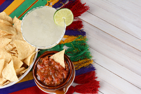 High angle view of a margarita cocktail with chips and salsa on a white rustic wood table. Horizontal format with copy space.