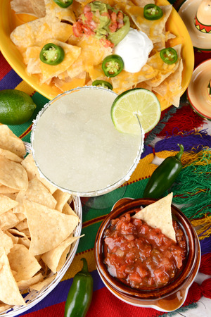 chips and salsa: Overhead view of a margarita cocktail surrounded by nachos, chips, salsa on a bright Mexican, table cloth. Vertical format. Cinco de Mayo theme.