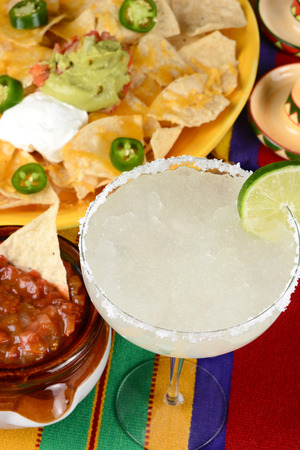 chips and salsa: High angle view of a margarita cocktail surrounded by nachos, chips, salsa on a bright Mexican, table cloth. Vertical format. Perfect for Cinco de Mayo projects.
