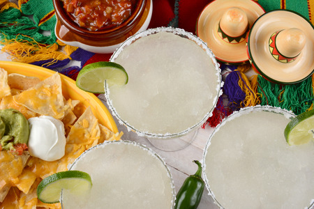 High angle view of three margarita cocktails surrounded by nachos, chips and salsa on a bright Mexican, table cloth. Horizontal format. Perfect for Cinco de Mayo projects. Stock Photo