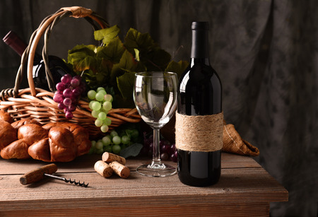 cork screw: Wine still life on a rustic wood table with warm afternoon window light. An old fashioned cork screw, a basket of grapes and leaves, a loaf of bread and some corks and an empty wineglass round out the scene. Stock Photo