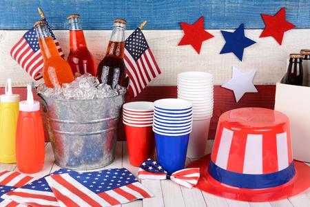 julio: Cuatro de Julio naturaleza muerta. Una mesa de picnic con un cubo de soda, banderas, el T�o Sam sombrero, 6 pack, ketchup y mostaza con una pared de color rojo, blanco y azul detr�s. Foto de archivo