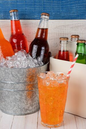white washed: An ice bucket full of soda bottles, a six pack carrier, and a glass of orange soda with straw. Closeup on a rustic set of white washed wood and one blue board. Stock Photo