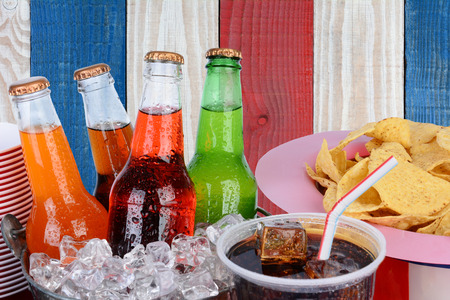 Cold soda bottles, cups and chips against a red white and blue background. Patriotic picnic image for 4th of July or Memorial Day projects. photo