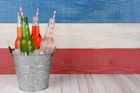 julio: Un cubo de botellas de soda con beber pajas contra un fondo rojo, blanco y azul para un 4 de picnic de julio, con copia espacio.