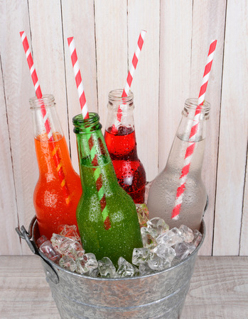flavoured: Closeup of an ice bucket of soda bottles shot from a high angle on a rustic wood picnic table. Four different open drinks with straws in the bottles. Stock Photo