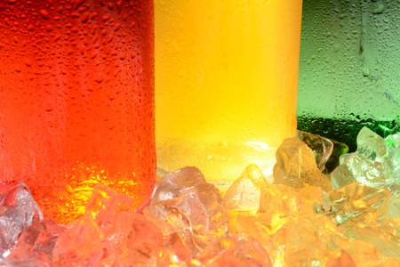 flavoured: An abstract closeup of three soda bottles in ice with condensation.