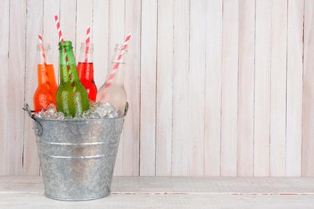 Un cubo de hielo de cuatro botellas de soda diferentes con pajitas de beber en un conjunto de madera blanca. Formato horizontal con espacio de copia.
