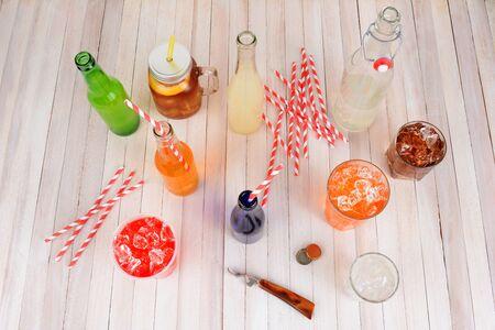 high angle shot: High angle shot of a group of assorted summer drinks. Lemonade, ice tea, soda, cola, orange soda and strawberry soda on a rustic wood table.
