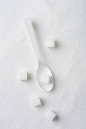 sugar cube: Overhead view of a white spoon, sugar cubes and granulated sugar. Stock Photo