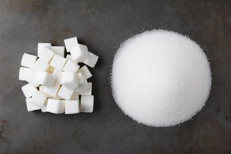 용된 베이킹 시트에 알갱이 흰 설탕의 더미와 설탕 큐브의 마운드의 오버 헤드보기.