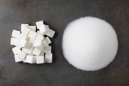 Overhead view of a pile of granulated white sugar and a mound of sugar cubes, on a used baking sheet. Standard-Bild