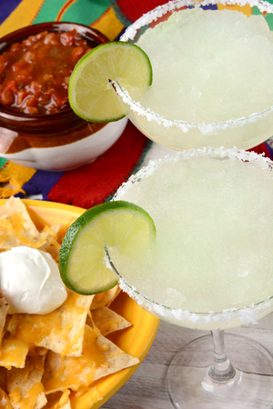 sour food: High angle view of two margarita cocktails for a Cinco de Mayo celebration. Surrounded by nacho chips and salsa on a bright Mexican table cloth. Stock Photo
