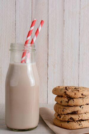 Close-up van een fles chocolademelk en een stapel van chocolade chip cookies in een rustieke keuken set.