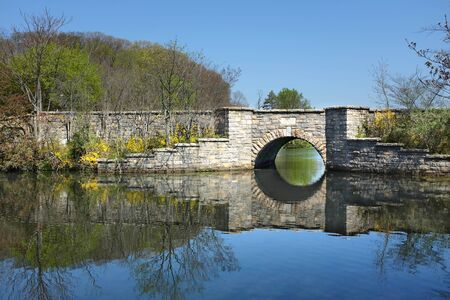 foot bridges: SETAUKET, NY - MAY 4, 2015: Bridge at Frank Melville Memorial Park. Constructed in 1937 and privately owned, the parks twenty-four acres include a circular walkway around the upper pond.